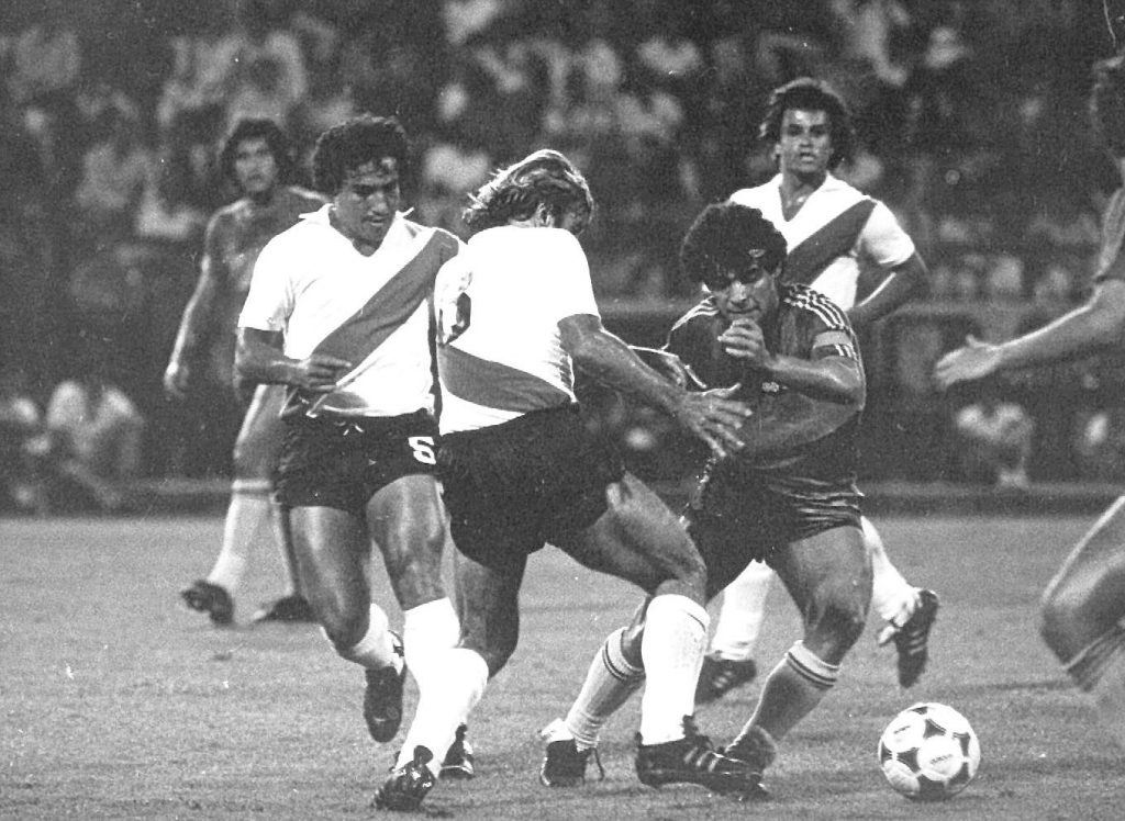 """Maradona intenta dejar en el camino a su """"sombra negra"""" del verano, otra vez """"Mostaza"""" Merlo, un año después. Detrás, Gallego. Dolió más saber que era la despedida de Boca que la derrota misma."""