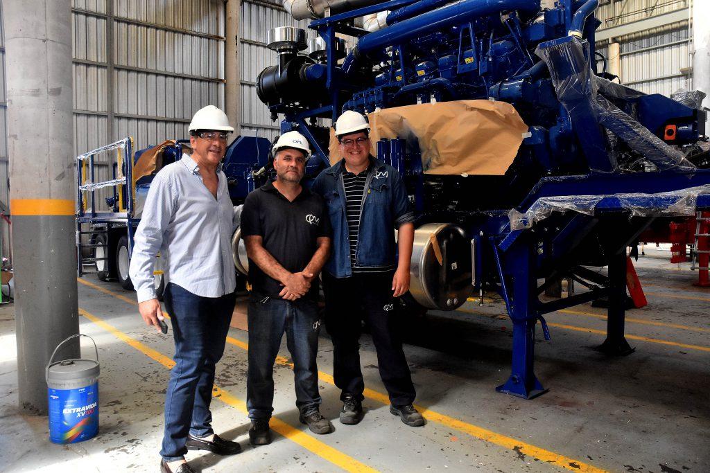 Guiscardo, junto a parte del personal de la compañía, posan para LA CAPITAL delante de un motor sometido a los últimos ajustes.