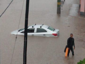 Un auto con el agua hasta casi llegar a las ventanas, en Caraza y Florencio Sánchez